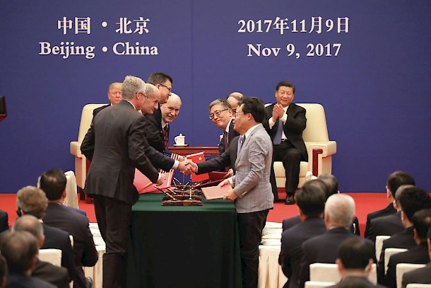 Walker peeks out for a photo during the signing of the LNG pipeline agreement in front of the presidents of the U.S. and China. Photo: Office of the Governor